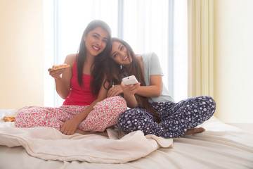 Two smiling young girls sitting on bed at home eating pizza and having fun watching television