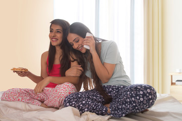 Two smiling young girls sitting on bed at home with one eating pizza and the other talking on mobile phone