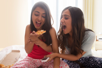 Two young girls sitting on bed at home sharing a pizza