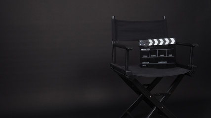 Clapperboard or movie slate with director chair use in video production ,film, cinema industry on black background.
