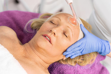 Woman in cosmetic hat receiving darsonvalization facial treatment