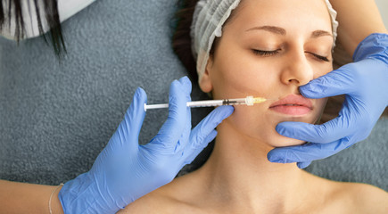Woman gets botox injection in her lips