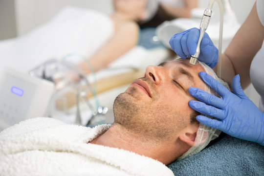 Man receiving cosmetic treatment of face