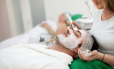 Man receiving hydration facial mask