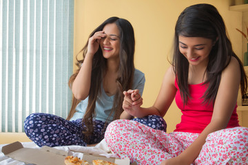 Two smiling young girls sitting on bed at home and talking with pizza in front