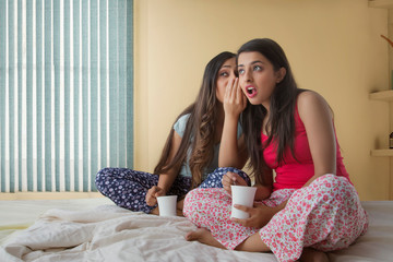 Two young girls sitting on bed at home holding coffee mugs and gossiping