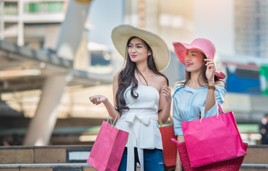 Both beautiful women are happy with the shopping.