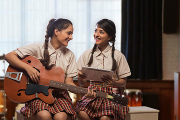 Two happy teenage school girls learning to play guitar in the music room at school