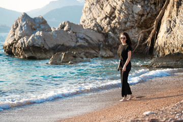 Young attractive woman walking on a sunny beach at shore. Traveler and blogger