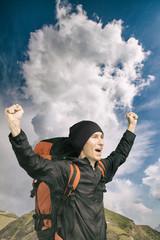 Young hiker shouting out on top with his hands raised, side view. Vertical.
