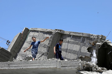 Palestinian boy dances on the rubble of a building during a musical event calling to boycott the Eurovision Song Contest hosted by Israel, in Gaza City