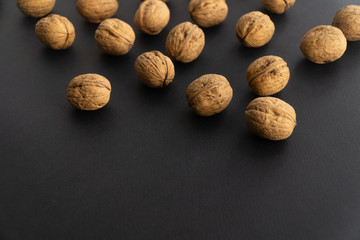 Walnuts in shell lying on black surface, side view. Healthy nuts and seeds background.