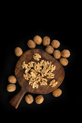 Cracked and whole walnuts lying on wooden carved cutting board and black table, top view. Healthy nuts and seeds composition.