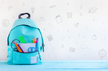 Concept back to school. Full turquoise School Backpack with stationery on table. Wall mural