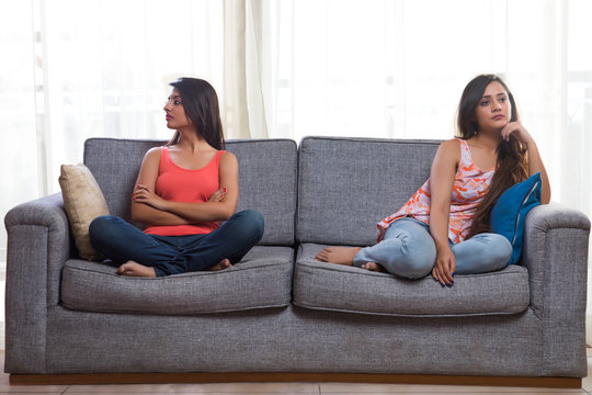 Two teenage girls sitting on two ends of a sofa looking in different directions