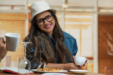 portrait of a smiling teenage girl wearing spectacles and a hat sitting at restaurant table holding a coffee cup