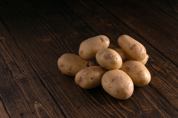 Heap of fresh clean potatoes on rustic wooden surface. Organic food, carbs, tubers.