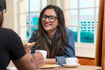 Smiling teenage girl in spectacles talking to friend sitting at restaurant eating pizza