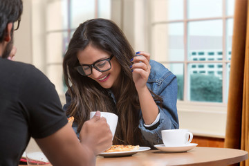 Smiling young girl in spectacles talking to friend sitting at restaurant having pizza and coffee