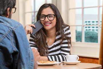 Smiling teenage girl in spectacles talking to friend sitting at restaurant holding her mobile phone to her cheek