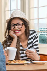 Smiling young girl wearing spectacles and hat sitting at restaurant table