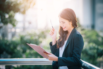 Portrait of business woman happy smile holding check list on clipboard and pen.