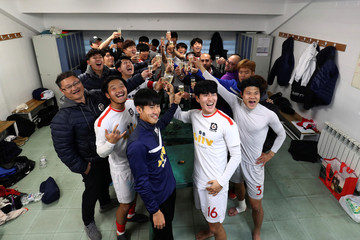 QUM FC team members celebrate a victory inside their dressing room in Illescas