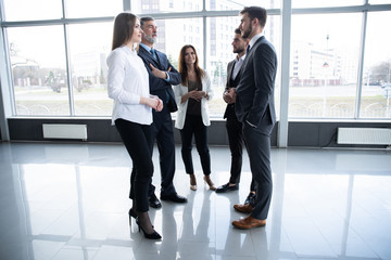 Group of Busy Business People Concept. Business team discussing work in office building hallway.