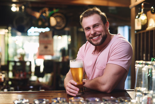 Portrait of smiling man drinking beer in the pub