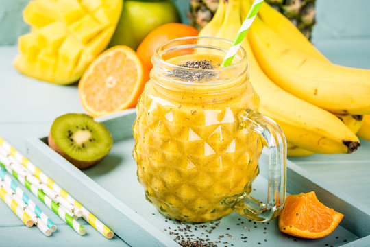 Exotic summer food concept with tropical fruits banana, orange, mango, pineapple, kiwi and yellow smoothie juice with chia seeds in glass.