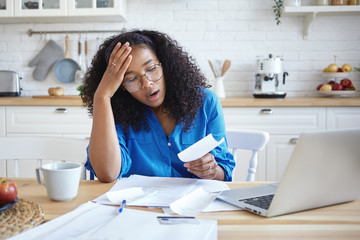 People, modern technology, finance and housework concept. Picture of tired young dark skinned woman in eyeglasses doing paperwork at home, having frustrated look, shocked with amount of debt