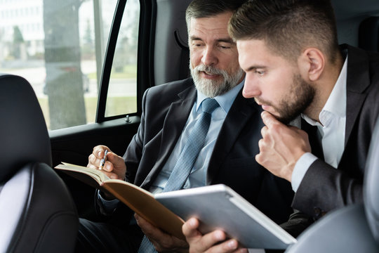 business colleagues discussing business ideas while sitting in backseat of the car or taxi.