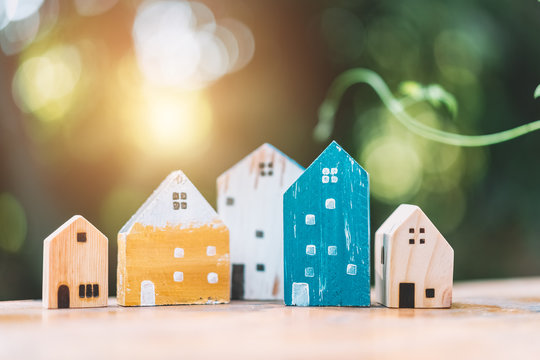 Small model houses on wooden table with nature green bokeh sunlight abstract background.