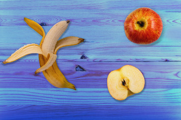peeled ripe banana and red apples on color wooden background. Healthy eating concept