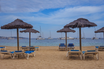 sun loungers and straw umbrellas on the sandy beach  of the Spanish town of Magaluf against the blue sea and white yachts