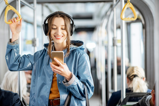 Young woman passenger standing with headphones and smartphone while moving in the modern tram, enjoying trip at the public transport