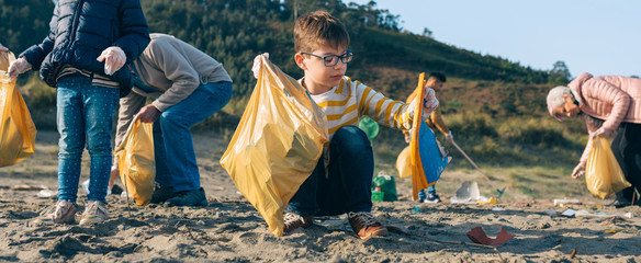 Boy picking up trash with group of volunteers on the beach
