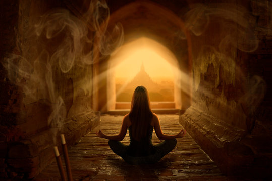 Woman meditating in buddhist temple