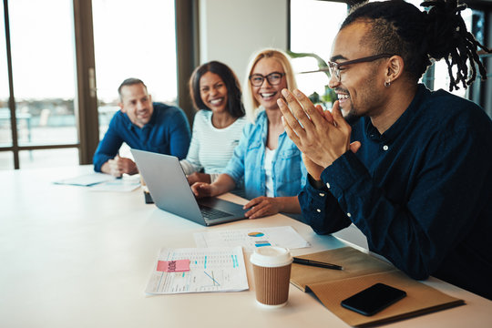African American office worker laughing with colleagues in a mee