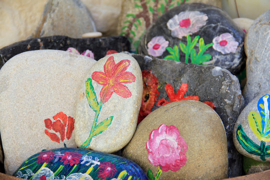 Handcraft artist paints on stone. Authentic pictures on natural stones for souvenirs and home decoration, greek domestic life