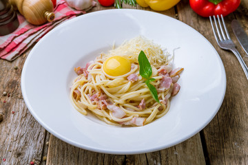 Spaghetti Carbonara with bacon on wooden background