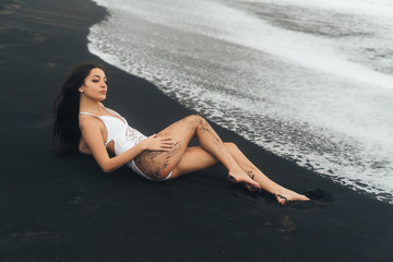 Portrait of happy girl with beautiful smile in swimsuit posing on black sand beach
