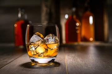 Spoed Foto op Canvas Alcohol Close up of single malt scotch whiskey, craft bourbon in round tumbler glass, on the rocks, with liquor bottles and rustic background