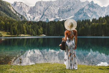 Young beautiful woman in a dress and hat near the lake