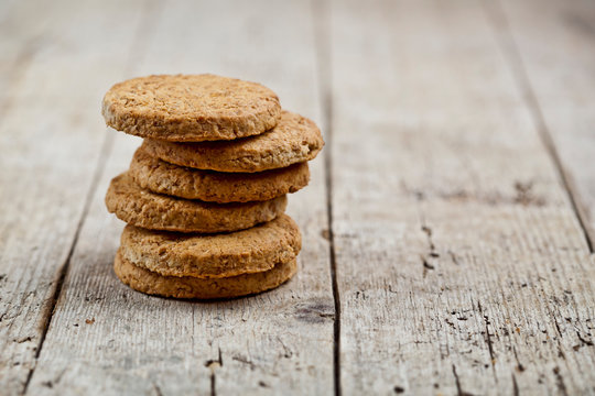 Stack of fresh baked oat cookies on rustic wooden table background.