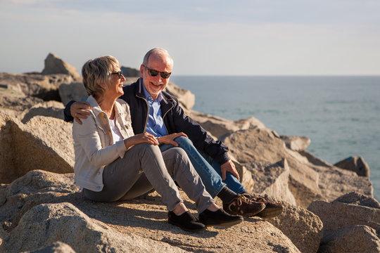 Happy senior couple sitting on rocks by the sea