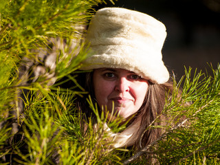 A young woman with gray eyes, a white hat and coat clothing hidden among the branches of trees