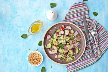 Light salad of crispy radish, cucumber and mint leaves with citrus dressing on a brown plate. Sprinkled with pine nuts. Top view.