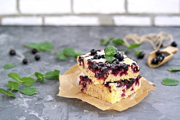 Sweet sliced cake with cornmeal and black currant. Decorated with fresh mint, powdered sugar and berries of frozen black currant.
