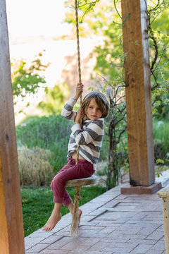 5 year old boy playing on swing under porch